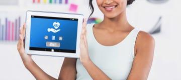 Image composée de femme d'affaires heureuse montrant le comprimé numérique dans le bureau créatif image libre de droits