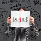 Image composée de femme d'affaires montrant une carte blanche devant son visage photos stock