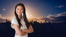 Image composée de femme d'affaires occasionnelle regardant l'appareil-photo avec des bras croisés Images libres de droits