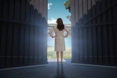 Image composée de femme d'affaires se tenant de nouveau à l'appareil-photo 3d Images stock