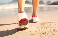 Image composée de femme d'ajustement marchant sur la plage image libre de droits