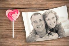 Image composée de femme de sourire étreignant son mari sur le divan par derrière Photographie stock