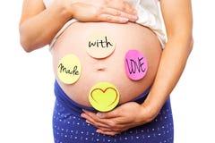 Image composée de femme enceinte avec des autocollants sur la bosse Photographie stock libre de droits