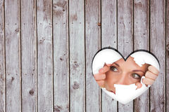 Image composée de femme regardant par le papier déchiré Image stock