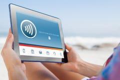 Image composée de femme se reposant sur la plage dans la chaise de plate-forme utilisant le PC de comprimé image libre de droits