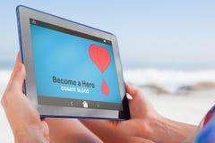 Image composée de femme se reposant sur la plage dans la chaise de plate-forme utilisant le PC de comprimé photos libres de droits