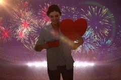 Image composée de femme tenant une carte de présent et de coeur Photo stock