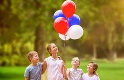 Image composée de fille avec des amis tenant les ballons colorés Image stock
