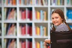 Image composée de fille se reposant dans le fauteuil roulant à l'école Photo stock