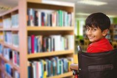 Image composée de garçon se reposant dans le fauteuil roulant à l'école Image stock
