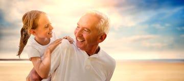 Image composée de grand-père tenant son petit-enfant sur le sien de retour Images libres de droits