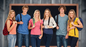 Image composée de groupe de sourire avec des sacs à dos dessus comme ils sourient Photographie stock libre de droits
