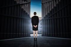 Image composée de jeune femme d'affaires se tenant avec des mains derrière 3d arrière Image stock