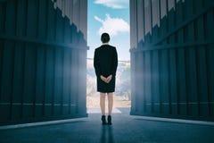 Image composée de jeune femme d'affaires se tenant avec des mains derrière 3d arrière Photographie stock