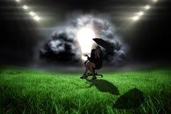 Image composée de jeune femme d'affaires tenant le parapluie Photos stock