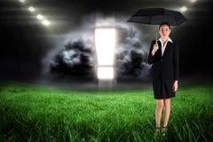 Image composée de jeune femme d'affaires tenant le parapluie Photo stock