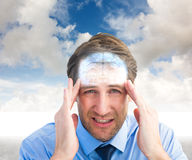 Image composée de jeune homme d'affaires avec le mal de tête grave image libre de droits
