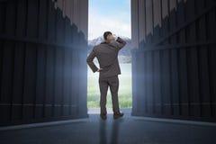 Image composée de jeune homme d'affaires se tenant de nouveau à l'appareil-photo rayant sa tête 3d Image libre de droits