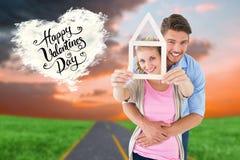 Image composée de jeunes couples étreignant et tenant le contour de maison photo stock