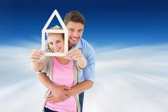 Image composée de jeunes couples étreignant et tenant le contour de maison images libres de droits