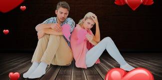 Image composée de jeunes couples attrayants se reposant tenant deux moitiés du coeur brisé 3D Images libres de droits