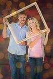 Image composée de jeunes couples attrayants tenant le cadre de tableau Photo stock