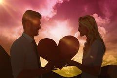Image composée de jeunes couples attrayants tenant le coeur rouge Photographie stock
