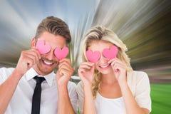 Image composée de jeunes couples attrayants tenant les coeurs roses au-dessus des yeux Image libre de droits
