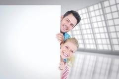 Image composée de jeunes couples de sourire se cachant derrière un signe vide Images stock