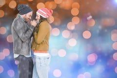 Image composée de jeunes couples en tissu chaud se tenant face à face et tremblant Photos stock