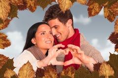 Image composée de jeunes couples faisant le coeur avec des mains Photos stock