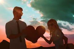 Image composée de jeunes couples frais tenant le coeur rouge Image libre de droits
