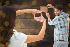 Image composée de jeunes couples heureux mettant vers le haut du cadre de tableau Images libres de droits