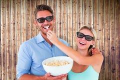 Image composée de jeunes couples heureux portant les lunettes 3d mangeant du maïs éclaté Image stock