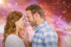 Image composée de jeunes couples heureux regardant l'un l'autre et le sourire Photos stock