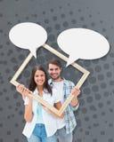 Image composée de jeunes couples heureux tenant le cadre de tableau Images libres de droits