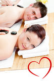 Image composée de jeunes couples mignons recevant un massage arrière avec les pierres chaudes Images stock