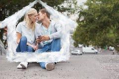 Image composée de jeunes couples mignons se reposant sur des baisers de planche à roulettes Images stock