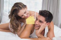 Image composée de jeunes couples romantiques dans le lit à la maison Photo stock