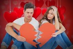 Image composée de jeunes couples se reposant sur le plancher avec le papier 3d de forme du coeur brisé Image stock