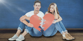 Image composée de jeunes couples se reposant sur le plancher avec le papier de forme du coeur brisé Images stock