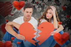 Image composée de jeunes couples se reposant sur le plancher avec le papier de forme du coeur brisé Image libre de droits