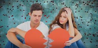Image composée de jeunes couples se reposant sur le plancher avec le papier de forme du coeur brisé Photos stock