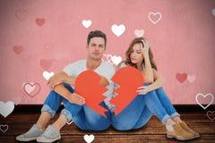 Image composée de jeunes couples se reposant sur le plancher avec le papier de forme du coeur brisé Image stock
