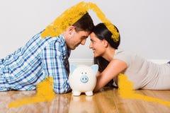 Image composée de jeunes couples se trouvant sur le plancher souriant avec la tirelire Photographie stock