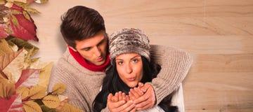 Image composée de jeunes couples soufflant au-dessus des mains Image stock