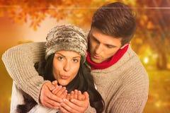 Image composée de jeunes couples soufflant au-dessus des mains photo stock