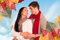 Image composée de jeunes couples souriant et étreignant Images stock