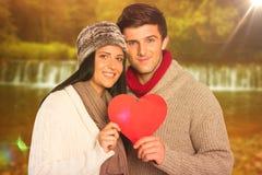 Image composée de jeunes couples souriant tenant le coeur rouge photos stock