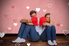 Image composée de jeunes couples tenant le coeur brisé Images stock